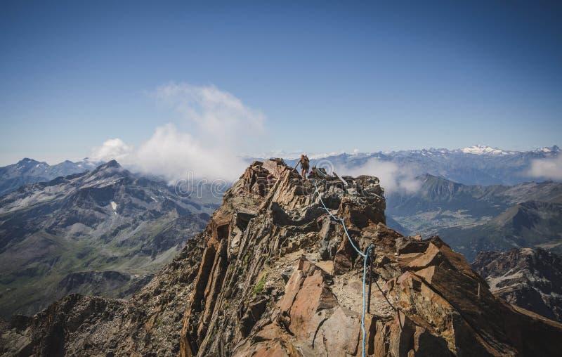 Mädchen, das entlang dem Gebirgsrücken, wenige Meter vor dem Quintino Sella-Schutz, italienische Alpen wandert stockfotografie