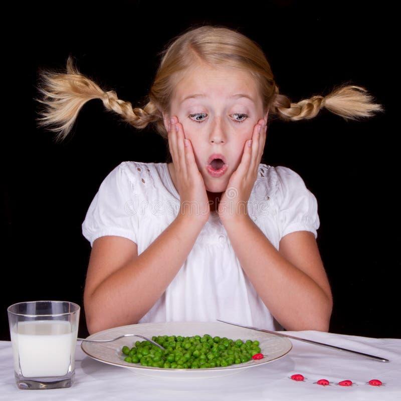Mädchen, das Erbsen mit Programmfehlern auf der Tabelle isst lizenzfreie stockfotos