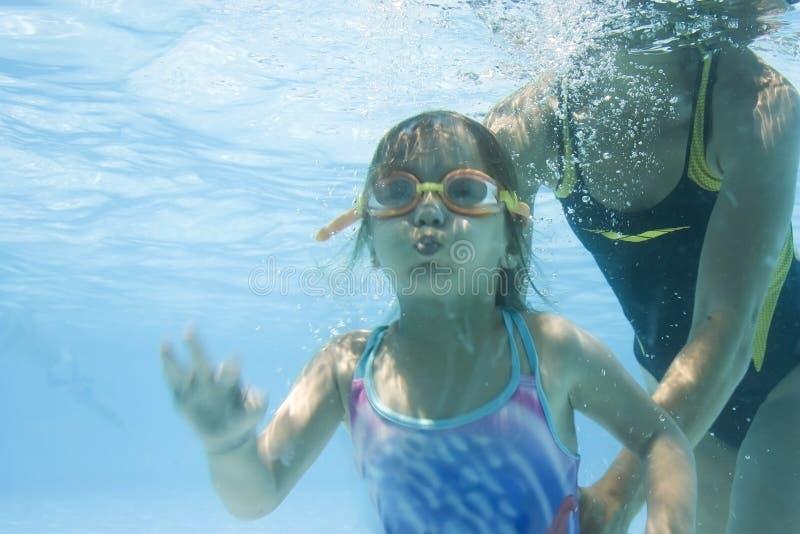 Mädchen, das erlernt, mit Mamma zu schwimmen stockbild