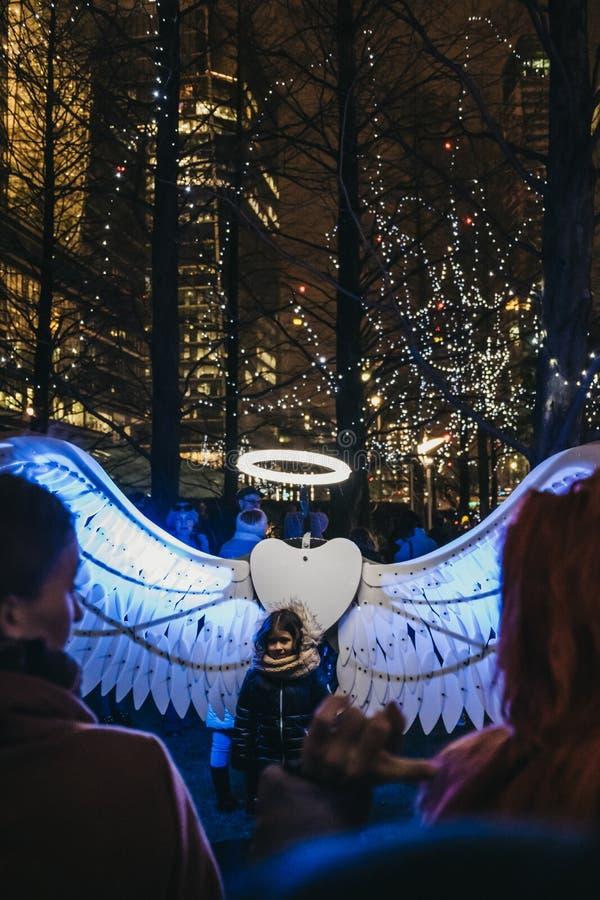 Mädchen, das für Foto im Winter-Lichtfestival in Canary Wharf, London, Großbritannien aufwirft lizenzfreie stockbilder
