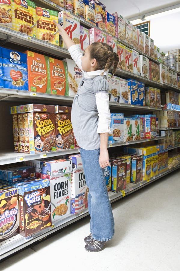 Mädchen, das für Getreideprodukt im Supermarkt erreicht lizenzfreie stockfotos