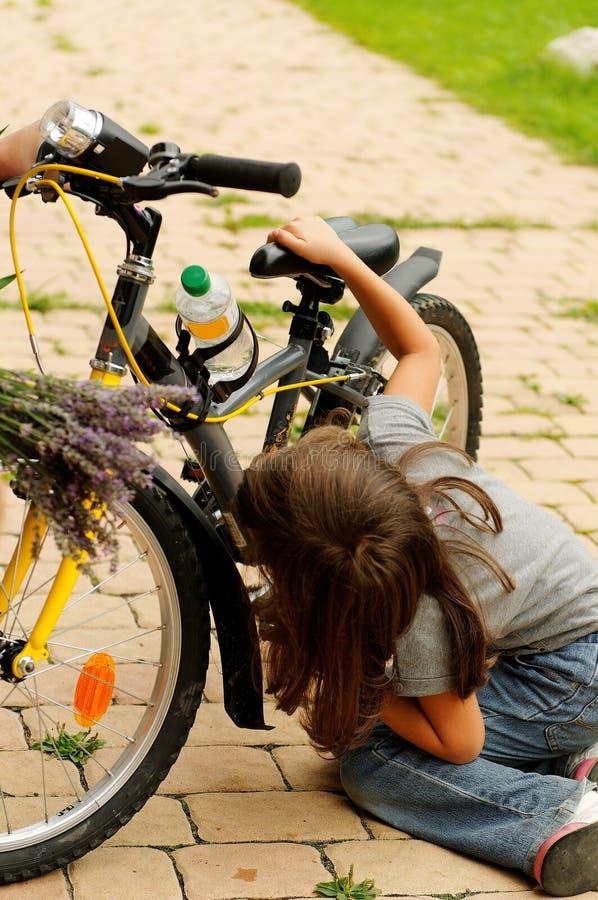Mädchen, das Fahrrad repariert   lizenzfreie stockfotos