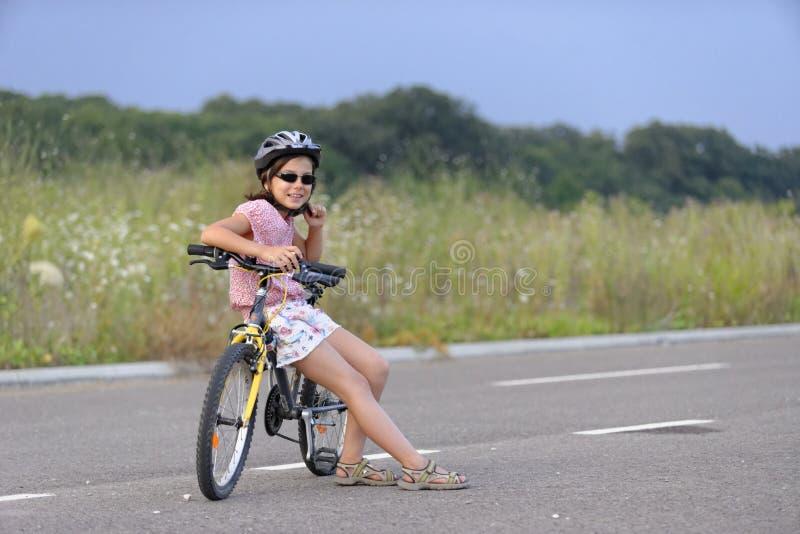 Mädchen, das am Fahrrad sich lehnt stockfoto