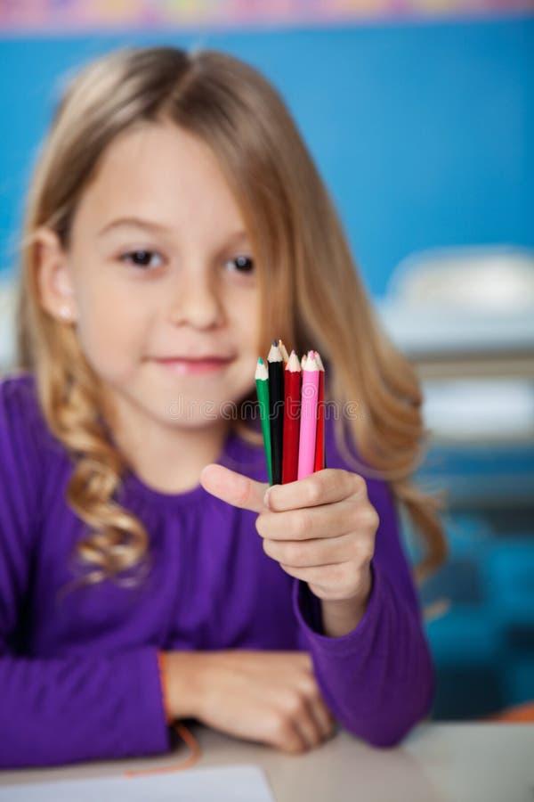 Mädchen, das Farbbleistifte im Kindergarten hält stockfotografie