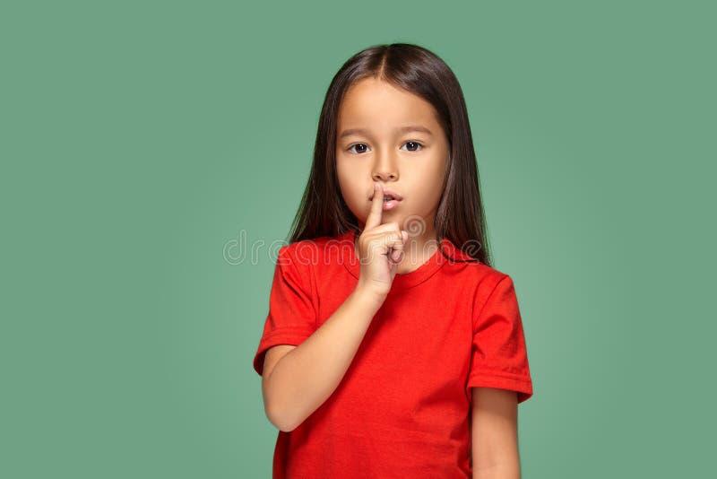 Mädchen, das Finger auf die Lippen bitten shh, ruhig, Ruhe setzt stockbild