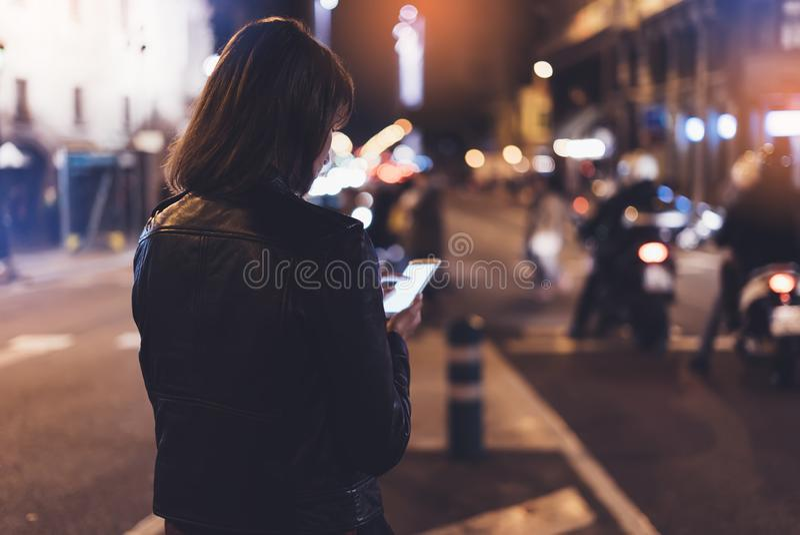 Mädchen, das Finger auf Schirm Smartphone auf Hintergrund bokeh Licht Nachtin der atmosphärischen Stadtstraße, Bloggerhippie-Mädc stockbilder