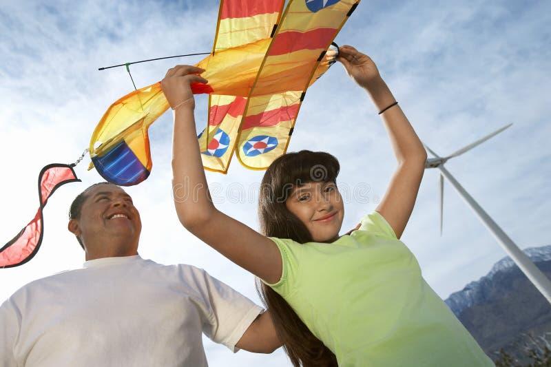 Mädchen, das Flugzeug-Drachen mit Vater hält stockfotos