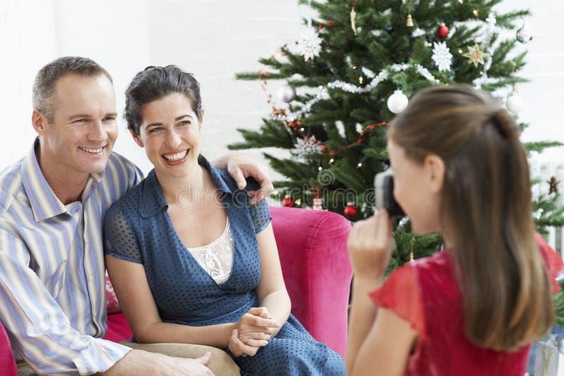 Mädchen, das Foto von Eltern durch Weihnachtsbaum macht lizenzfreie stockbilder