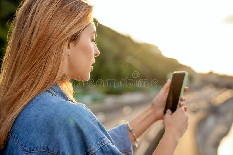 Mädchen, das Fotos einer Landschaft, Nahaufnahme eines Telefons in ihr macht stockbild