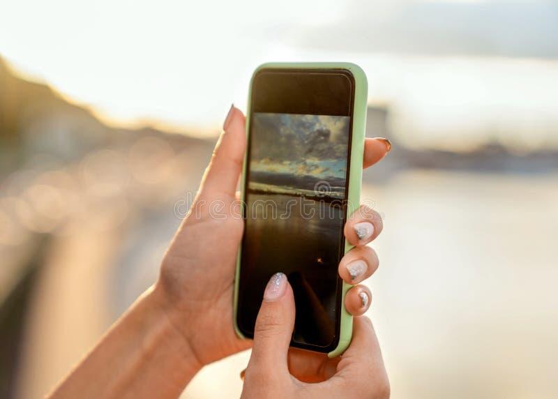 Mädchen, das Fotos einer Landschaft, Nahaufnahme eines Telefons in ihr macht lizenzfreies stockfoto