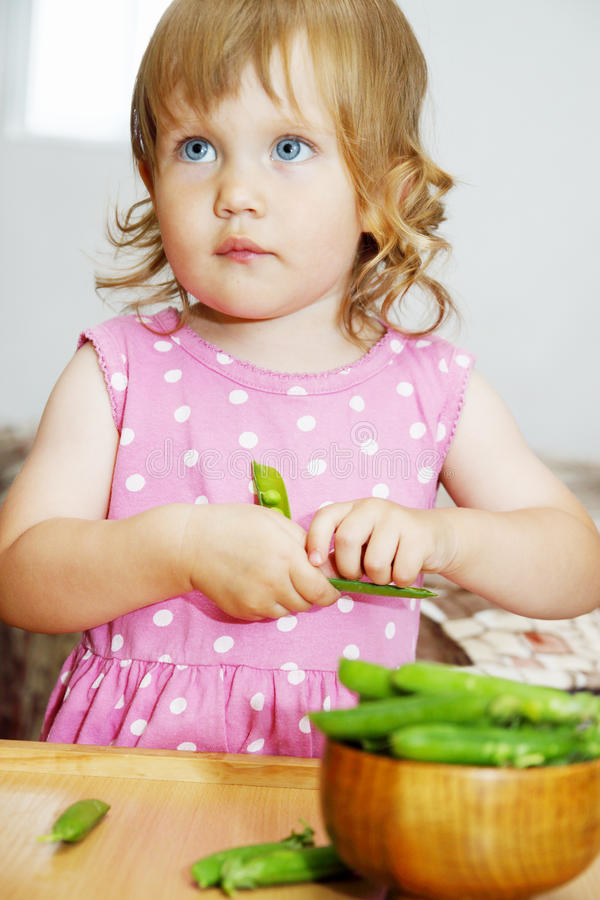 Mädchen, das frische Erbsen isst stockbild