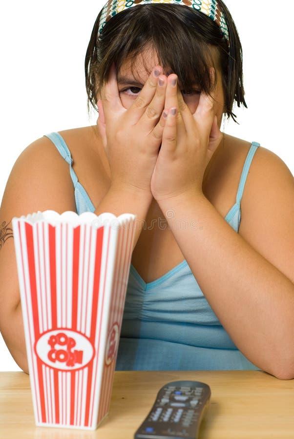 Mädchen, das furchtsamen Film überwacht lizenzfreies stockfoto