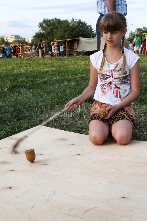 Mädchen, das ` gasing ` oder das Spitzenspinnen, ein russisches traditionelles altes spielt lizenzfreies stockbild