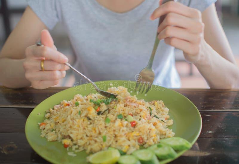 Mädchen, das gebratenen Reis auf Weichzeichnung isst stockbilder