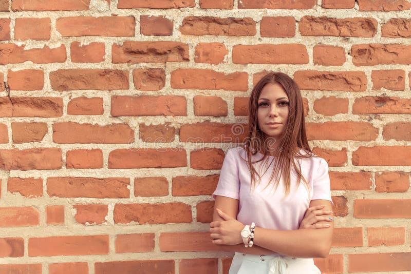 Mädchen, das gegen Hintergrund einer alten Wand des roten Backsteins aufwirft Freier Platz für Text Ernster Blick Im Sommer in de lizenzfreies stockbild