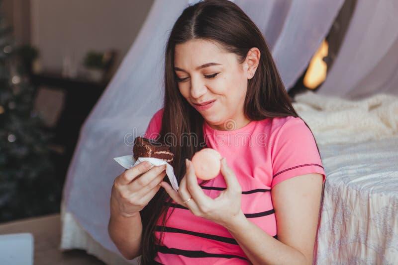 Mädchen, das geschmackvollen browny Kuchen mit in Schlafzimmer isst Süßer Nachtisch Guten Morgen stockfotografie