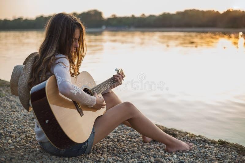 Mädchen, das Gitarre beim Sitzen auf dem Strand spielt stockbild