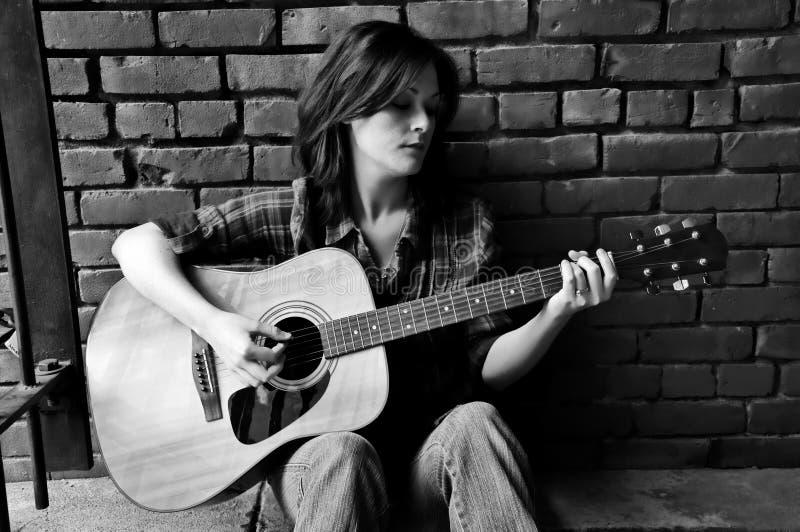Mädchen, das Gitarre spielt lizenzfreie stockfotografie