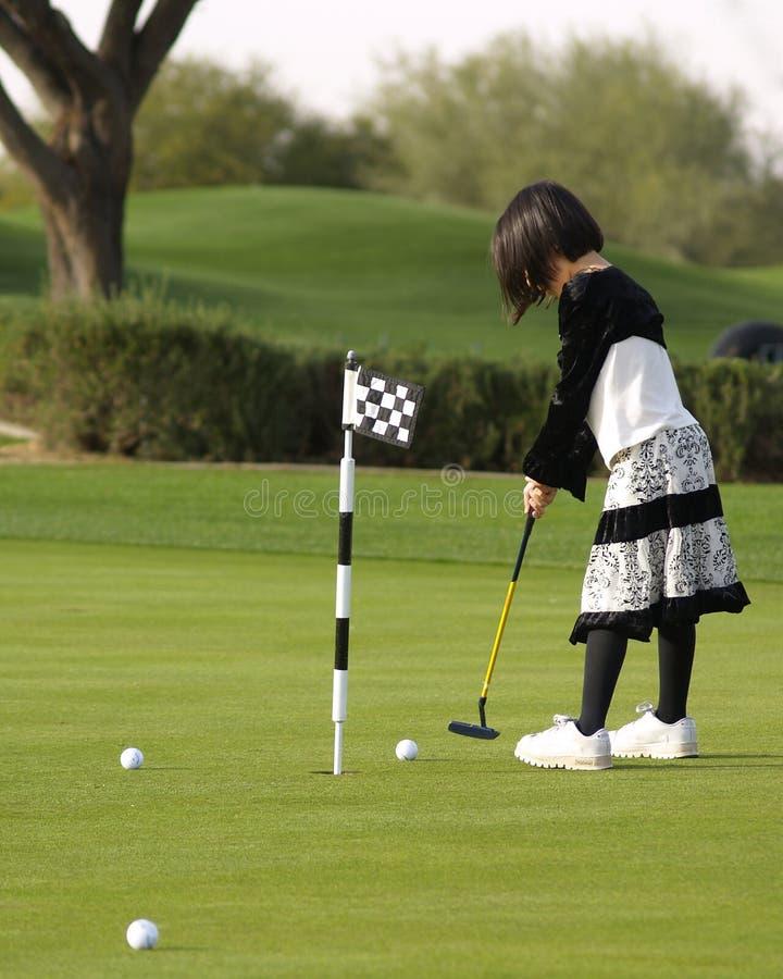 Mädchen, das Golf spielt stockbild