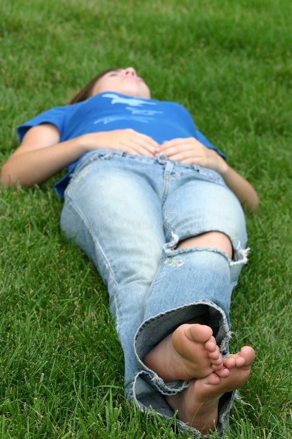 Mädchen, das in Gras legt stockbild