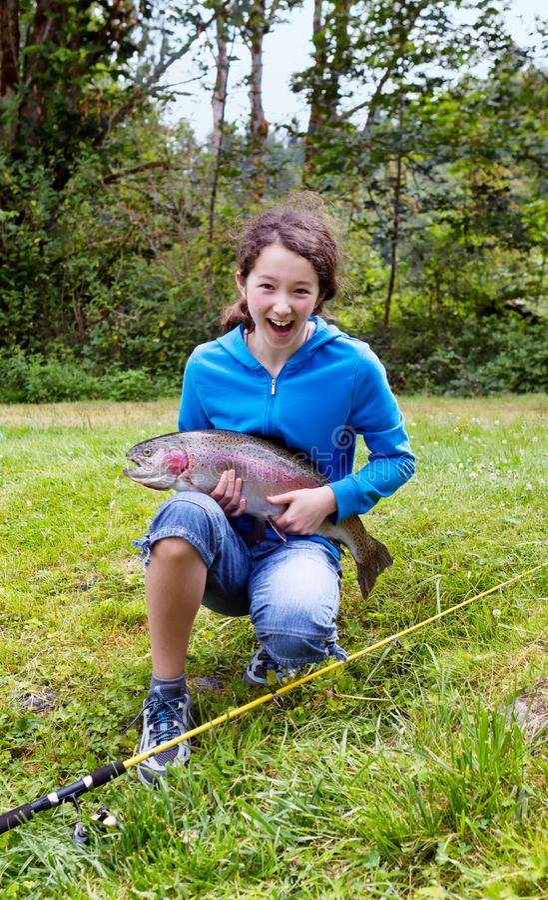 Mädchen, das große Regenbogenforelle mit enormem Lächeln hält lizenzfreie stockfotos