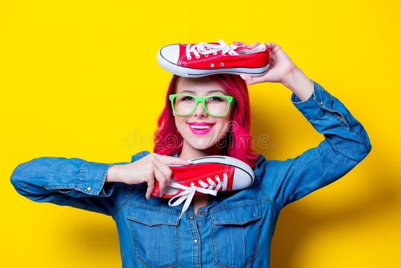 Mädchen, das Gummiüberschuhe eines Wunschrotes hält stockbilder