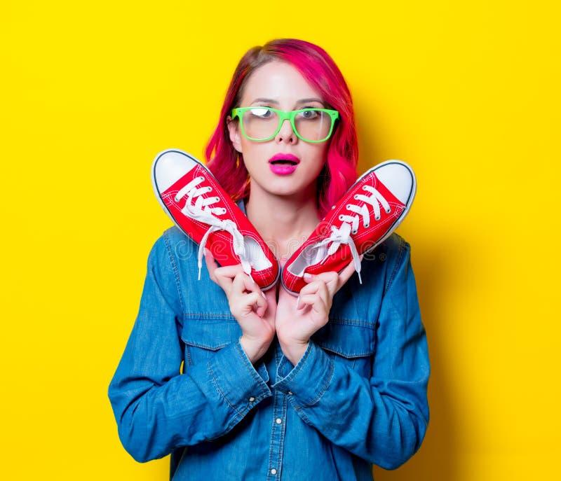 Mädchen, das Gummiüberschuhe eines Wunschrotes hält lizenzfreies stockbild