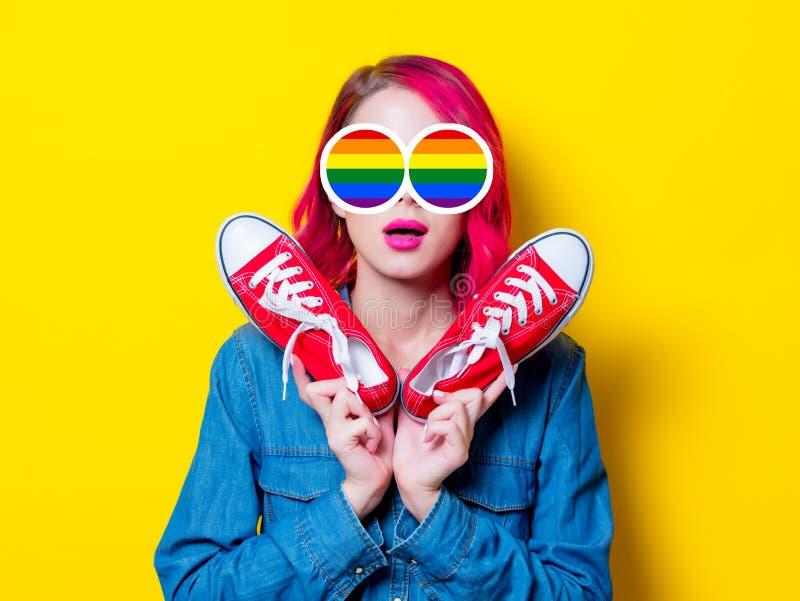 Mädchen, das Gummiüberschuhe eines Wunschrotes hält stockfoto