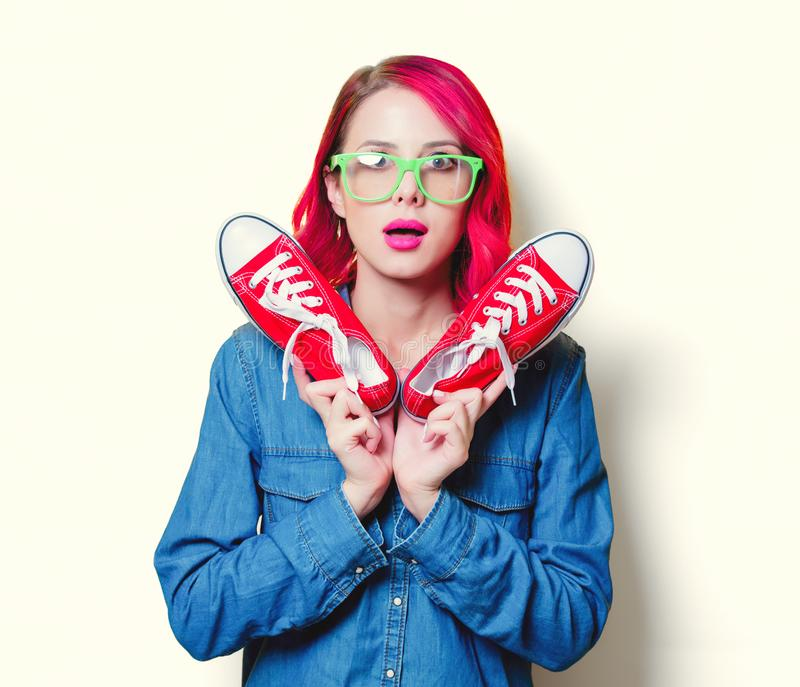 Mädchen, das Gummiüberschuhe eines Wunschrotes hält lizenzfreies stockfoto