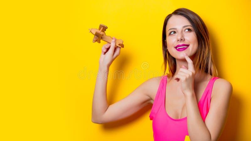 Mädchen, das hölzernes Spielzeugflugzeug hält stockfotografie