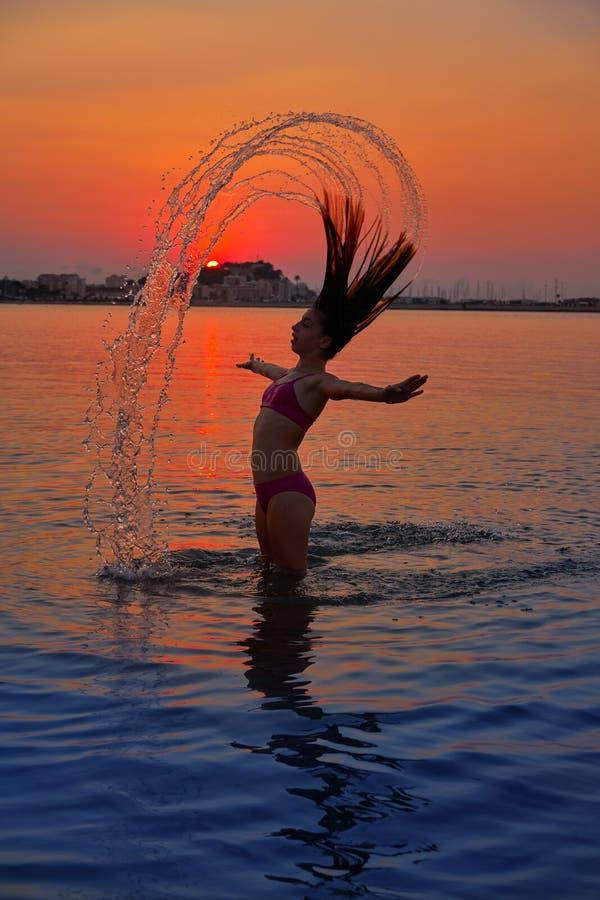 Mädchen, das Haarleichten schlag am Sonnenuntergangstrand leicht schlägt lizenzfreies stockfoto