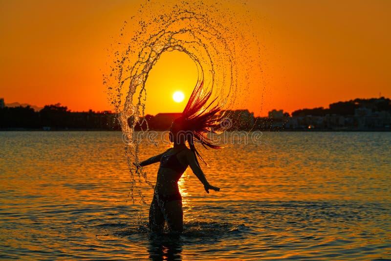 Mädchen, das Haarleichten schlag am Sonnenuntergangstrand leicht schlägt stockfotos