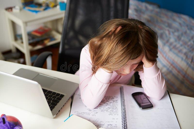 Mädchen, das Handy verwendet, anstatt zu studieren im Schlafzimmer stockbilder