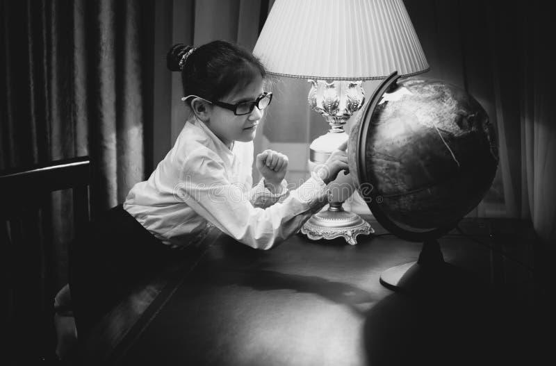 Mädchen, das Hausarbeit tut und Kugel betrachtet stockfotografie
