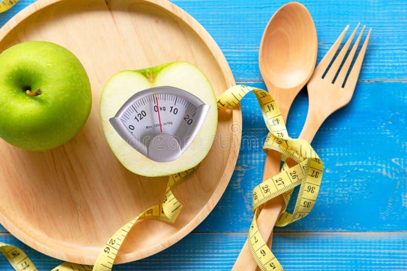 Mädchen, das helles Sandwich - Diät isst Grüner Apfel mit Gewichtsskala und messendes Band für Balancenkörpergewichtsverlust im g lizenzfreies stockfoto