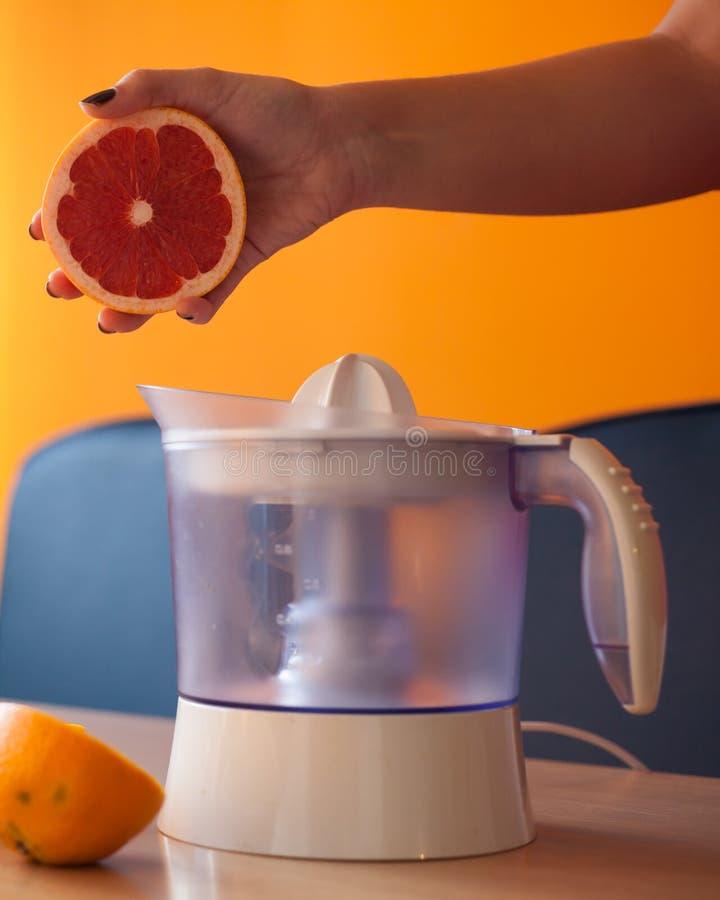Mädchen, das heraus Hälfte einer Pampelmuse hält, bevor sie mit einem elektrischen Zitrusfrucht Juicer zusammengedrückt wird lizenzfreie stockfotos