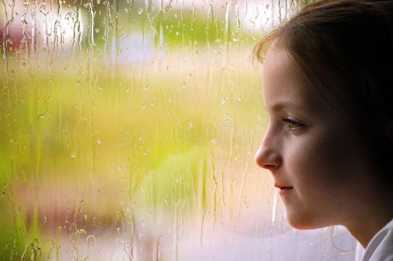 Mädchen, das heraus regnerisches Fenster schaut stockfotos