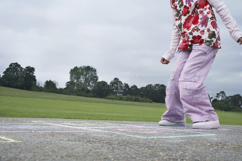 Mädchen, das Hopse im Spielplatz spielt lizenzfreie stockfotografie