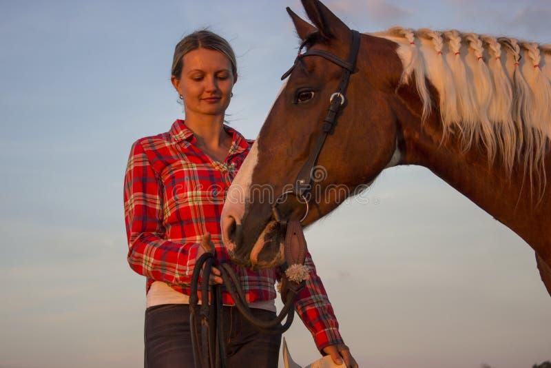 Mädchen, das ihr Pferd und Himmel liebt stockfoto