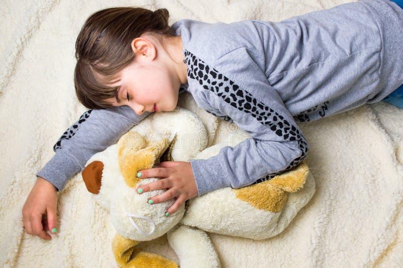Mädchen, das ihr Spielzeug umarmend ein Schläfchen hält lizenzfreie stockbilder