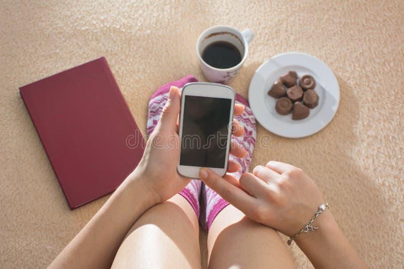 Mädchen, das ihr Telefon im Bett verwendet stockfotografie