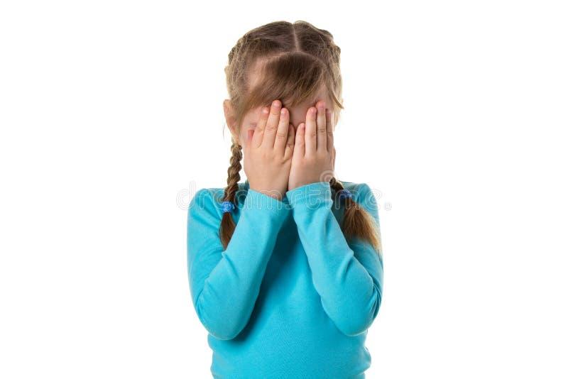 Mädchen, das ihre Augen durch die Hände, lokalisiert auf dem weißen Hintergrund bedeckt stockfoto