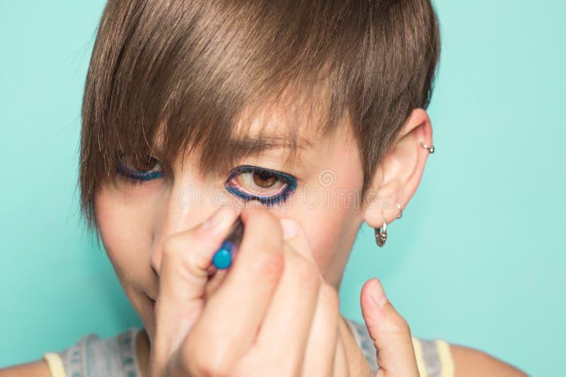 Mädchen, das ihre Augen malt Frau im Make-up lizenzfreie stockfotos