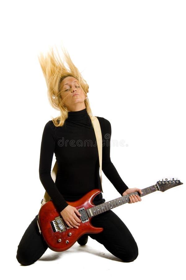 Mädchen, das ihre elektrische Gitarre auf Knien spielt lizenzfreie stockbilder
