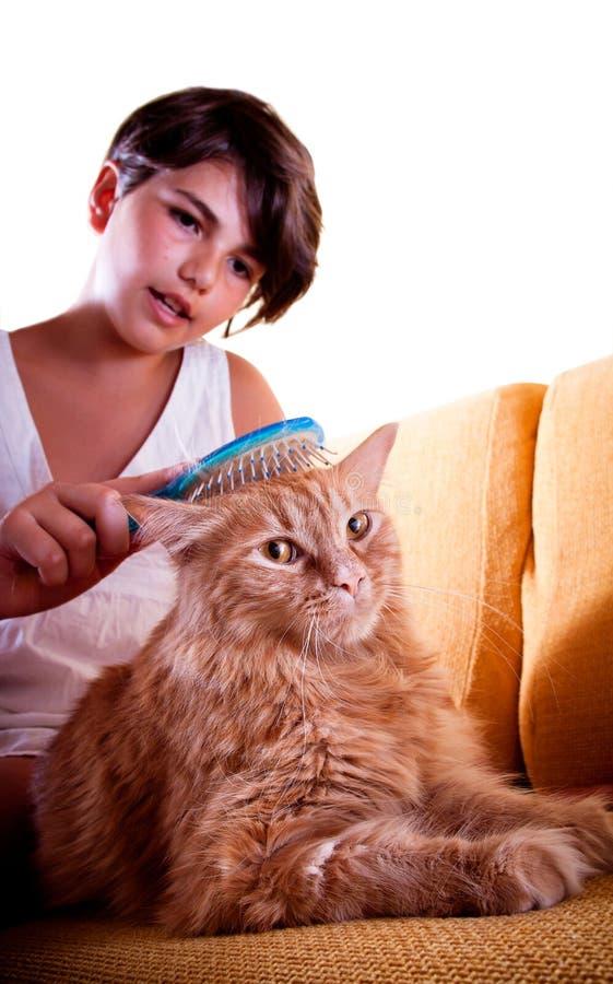 Mädchen, das ihre Katze pflegt lizenzfreies stockbild