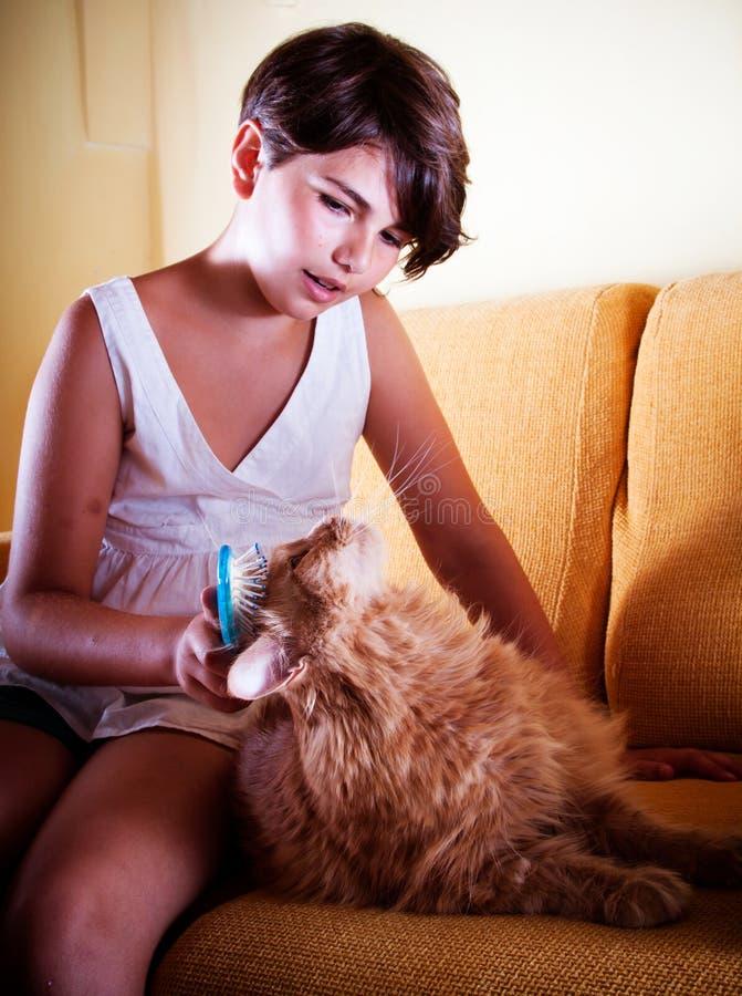 Mädchen, das ihre Katze pflegt stockfotografie
