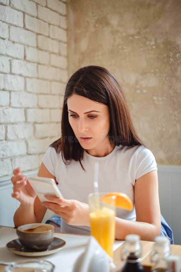 Mädchen, das ihrem Handy im Restaurant entsetzt betrachtet stockfotos
