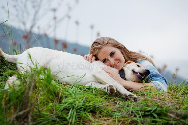 Mädchen, das ihren Hund umarmt stockbilder