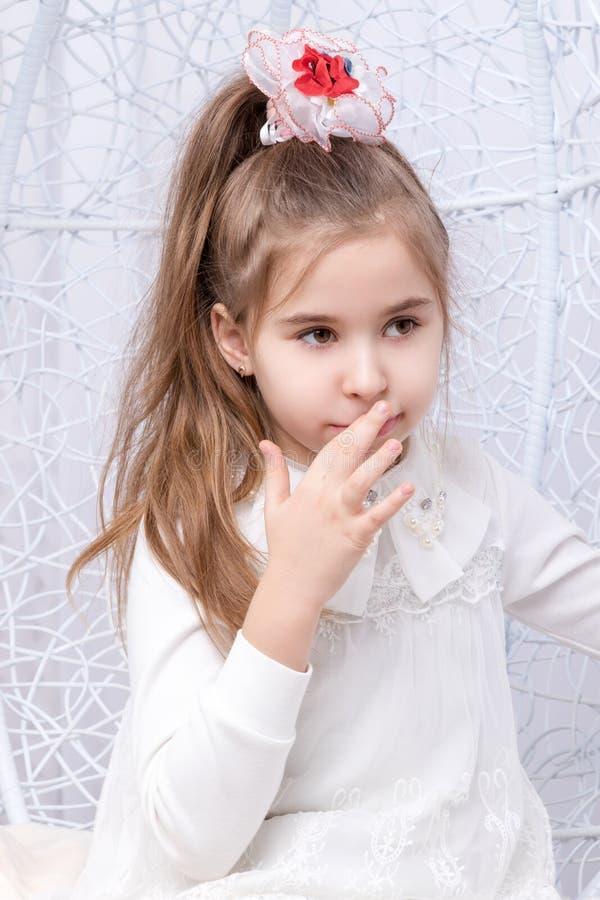 Mädchen, das ihren Mund durch Finger berührt stockfotografie