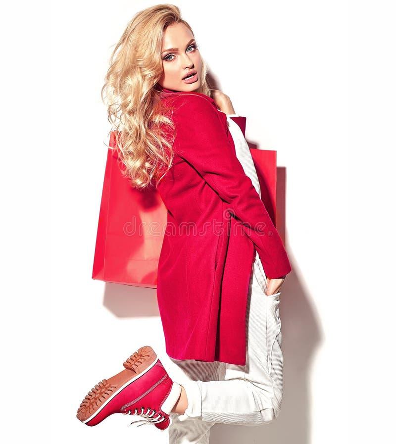Mädchen, das in ihrer Handgroßen Einkaufstasche in der roten Kleidung des Hippies lokalisiert auf Weiß hält stockfotografie